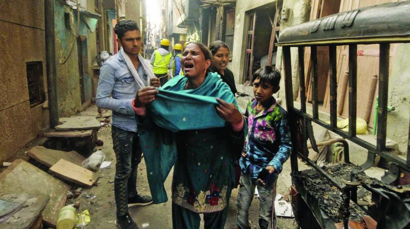 People react after their houses were torched by a violent mob at Karwal Nagar in Northeast Delhi on Wednesday. (Photo: Pritam Bandyopadhyay)