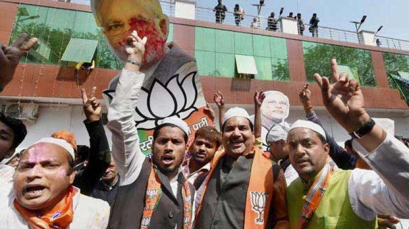 BJP supporters celebrate as early trends show the party's win in the last Uttar Pradesh and Uttarakhand assembly polls, at the party office in Lucknow. (PTI)