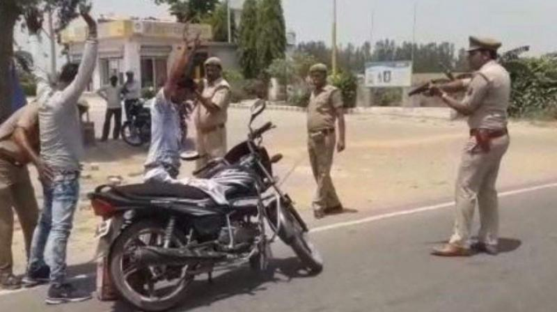 A video and some photographs of the policemen frisking people and checking their vehicles with one policeman pointing a gun at them, forcing them to stand motionless in hands-up position has gone viral on various social media platforms. (Photo: ANI)