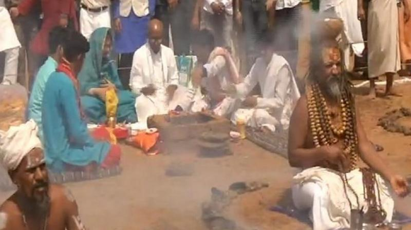At the 'pooja' Digvijaya is seen dressed in white kurta pyjama seated on the ground while others surround him in a semi circle. (Photo: ANI)