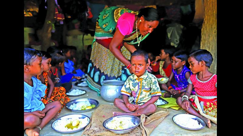 Children are being served hot meal at Satyagaon Anganwadi centre in Odisha.