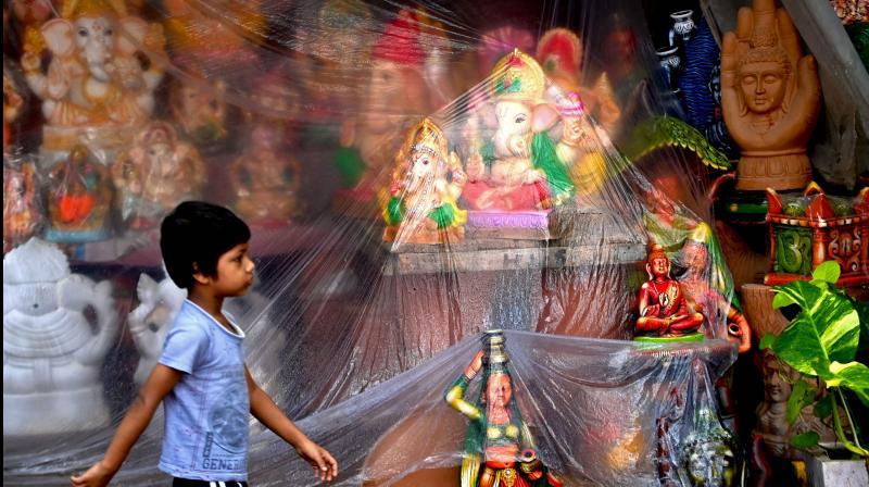 A child walks past idols of the elephant-headed Hindu god Ganesha displayed for sale along the roadside ahead of the Ganesh Chaturthi festival in New Delhi on September 6, 2021. (Money SHARMA / AFP)