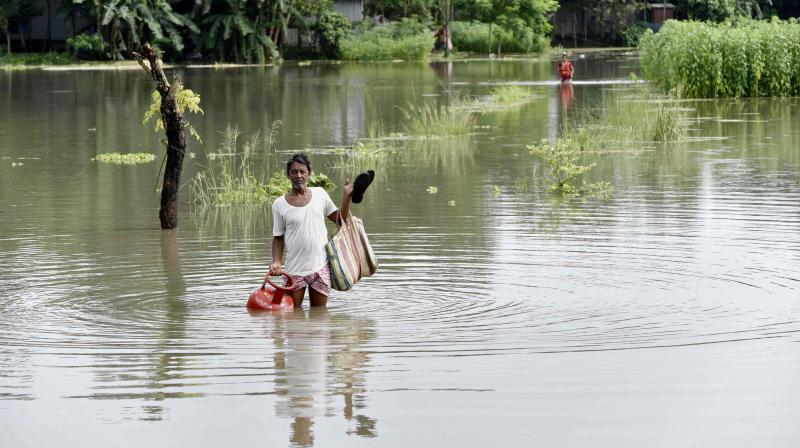 A villager carries a cooking gas cylinder as he wades through floodwaters at Jania village in Barpeta, Assam, on Saturday. ( PTI)