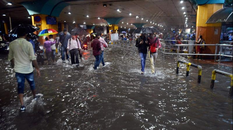 Commuters walk through flooded streets after heavy rains lashed at Thane in Mumbai on Tuesday. (Photo: PTI)