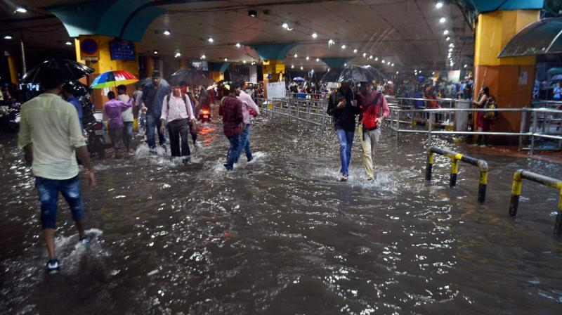 People walk through a waterlogged street following heavy rains in Mumbai. Heavy rains Tuesday brought Mumbai to a halt flooding vast areas of the city. (Photo: PTI)