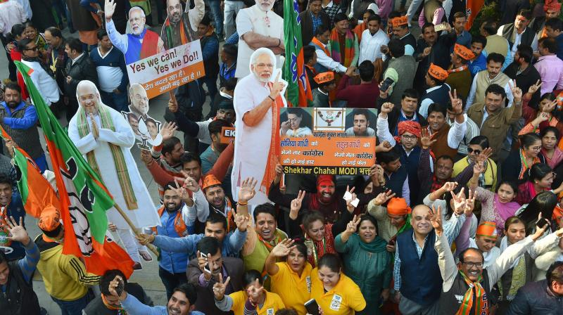 BJP workers celebrate with the cut-outs of Prime Minister Narendra Modi and party president Amit Shah at the party headquarters in New Delhi on Monday, after the party's victory in the Assembly elections in Gujarat on Himachal Pradesh. (Photo: PTI)