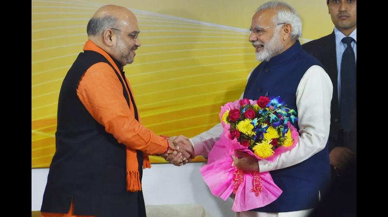 Prime Minister Narendra Modi being greeted by BJP President Amit Shah at a felicitation function in New Delhi on Monday, after the party's win in Gujarat and Himachal Pradesh Assembly elections. (Photo: PTI)