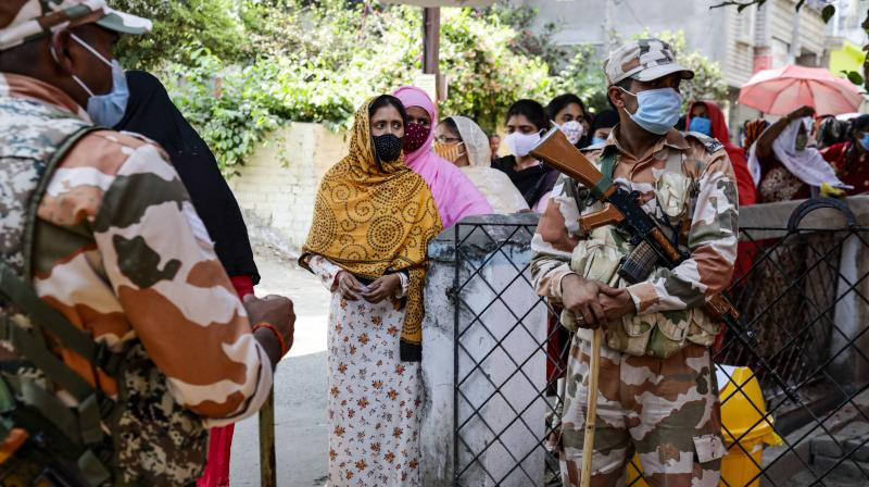 Indian paramilitary soldiers stand guard near a polling booth as voters wait to cast their votes during the fifth phase of West Bengal state elections in Newtown Rajarhat, North 24 Parganas district, India, Saturday, April 17, 2021. (AP)