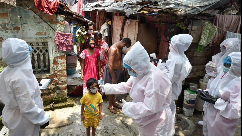 Health workers wearing protective gear during a door-to-door thermal screening at a slum area to detect COVID-19 positive cases, amid the ongoing nationwide lockdown, in Kolkata. PTI photo