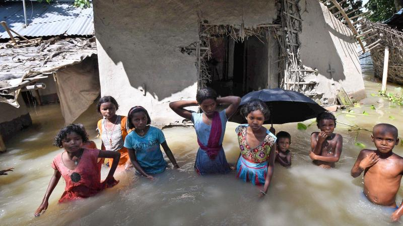 Children stand  waist-deep in flood water as they wait for rescue workers in Katihar on Saturday. (Photo: PTI)