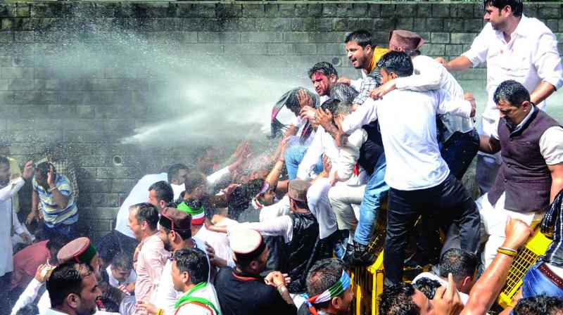 Youth Congress activists being sprayed with watercanons during a protest outside Vidhan Sabha in Shimla on Friday. (Photo: PTI)