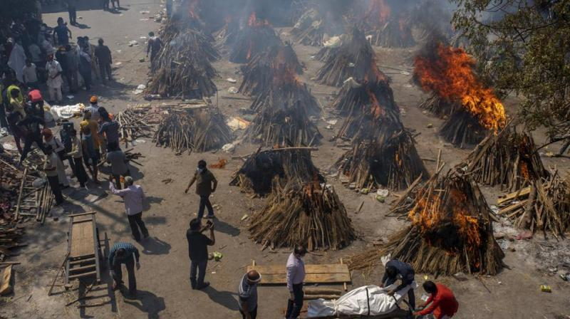 In this file photo, multiple funeral pyres of victims of COVID-19 burn at a ground that has been converted into a crematorium for mass cremation in New Delhi. (Photo: AP)
