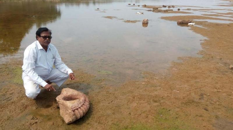 Researcher Nrusingha Charan Sahoo with a piece of Buddhist sculpture. (Photo: Asian Age)