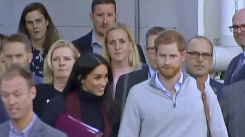 In this image made from video, Britain's Prince Harry, center right, and his wife Meghan, center left, Duke and Duchess of Sussex, approach a car at an airport in Sydney, Monday, Oct. 15, 2018. (Photo: AP)