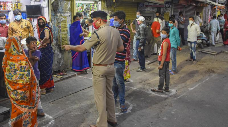 People stand in a queue at safe distance to buy grocery items from a shop during the nationwide lockdown imposed in wake of coronavirus pandemic, in Bhopal on Sunday. PTI photo