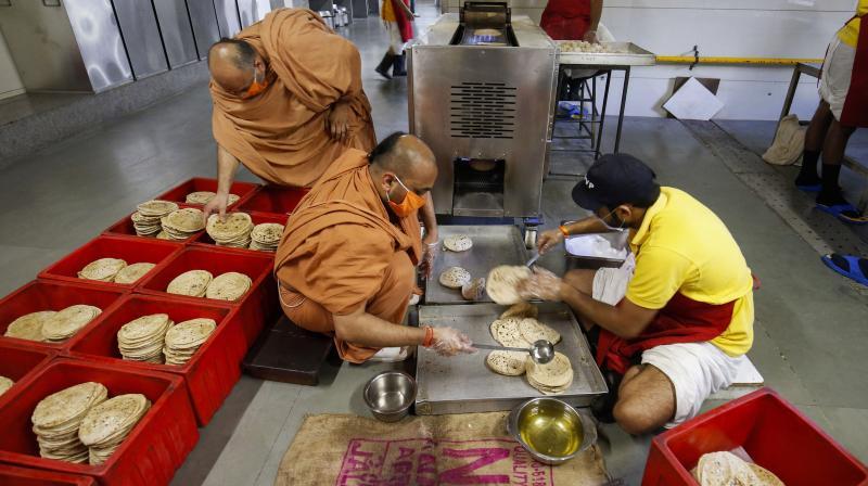 Members of Swaminarayan Gurukul Vishwavidya Pratishthanam (SGVP) pack food to be distributed amongst the poor and homeless people during the nationwide lockdown, in wake of coronavirus outbreak, in Ahmedabad. PTI photo