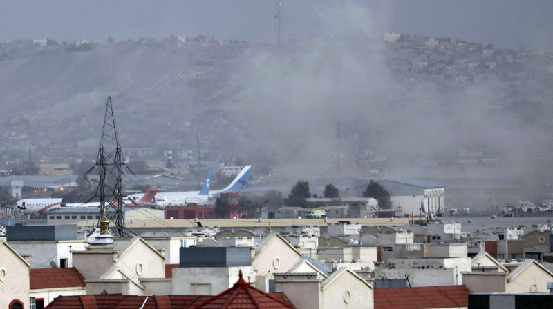 Smoke rises from a deadly explosion outside the airport in Kabul, Afghanistan, Thursday, Aug. 26, 2021. Two suicide bombers and gunmen have targeted crowds massing near the Kabul airport, in the waning days of a massive airlift that has drawn thousands of people seeking to flee the Taliban takeover of Afghanistan. (AP/Wali Sabawoon)