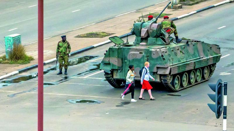 Young women walk past an armoured personnel carrier at an intersection as Zimbabwean soldiers regulate traffic in Harare. (Photo: AFP)