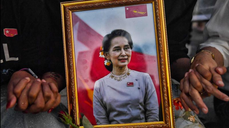 A picture of detained civilian leader Aung San Suu Kyi is seen as Myanmar migrants living in Thailand hold hands during a memorial in Bangkok on March 4, 2021 to honour those who died during demonstrations against the military coup in their homeland. (Lillian SUWANRUMPHA / AFP)