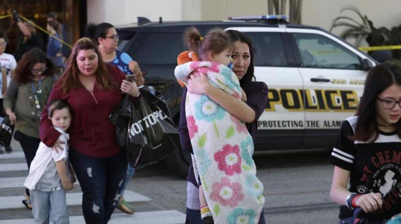 San Antonio police help shoppers exit the Rolling Oaks Mall in San Antonio, after a deadly shooting. Authorities say several were injured after a robbery at the shopping mall. (Photo: AP)