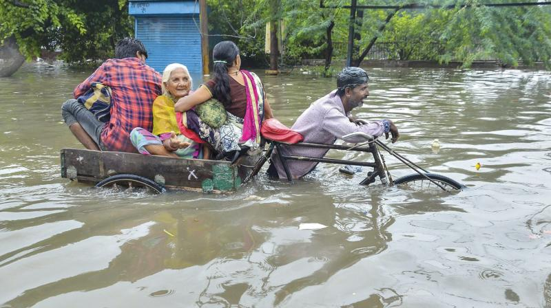 A rickshaw puller ferries passengers through a water-logged street during heavy rain in Mathura on Friday. (Photo: PTI)