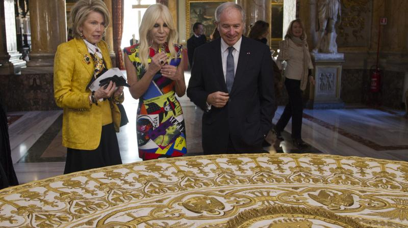 From left, Christine Hearst Schwarzman, Donatella Versace and Stephen A. Schwarzman, CEO of Blackstone, look at a liturgical vestment of pope Benedict XV, in Rome, Monday, Feb. 26, 2018. (Photo: AP)