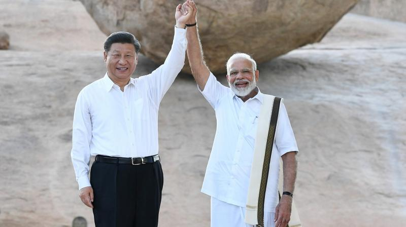 Chinese President Xi Jinping and Indian Prime Minister Narendra Modi raise hands together at Arjuna's Penance in Mamallapuram, India. (Photo: AP)