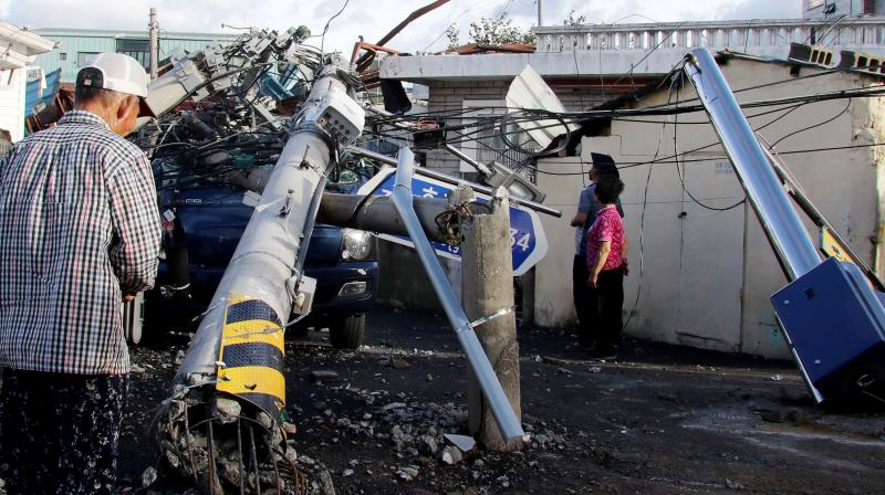 People look at an electric pole downed by Typhoon Maysak in the southeastern port city of Ulsan on September 3, 2020. - At least one person was killed and more than 2,000 people evacuated to temporary shelters in South Korea as a powerful typhoon churned across the peninsula, authorities said on September 3. (AFP)