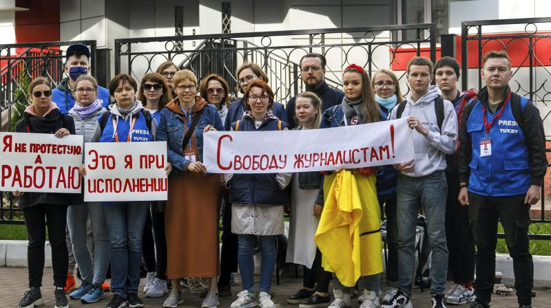 Journalists of Belarusian TUT.BY media outlet hold banners reading