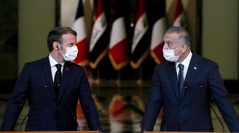French President Emmanuel Macron (L) and Iraq's Prime Minister Mustafa al-Kadhemi, mask-clad due to the COVID-19 coronavirus pandemic, give a joint press conference in Baghdad on September 2, 2020. - Macron landed in Baghdad on his first official trip to Iraq, where he hopes to help the country reassert its