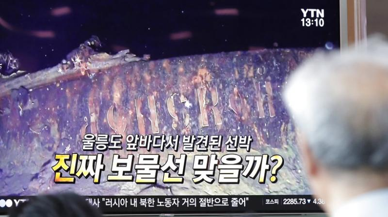People watch a TV screen showing the news program reporting about a sunken Russian warship at the Seoul Railway Station in Seoul, South Korea, Thursday, July 19, 2018. A South Korean company's claim to have found a sunken Russian warship has triggered investor frenzy amid unconfirmed rumors that the ship was carrying 200 tons of gold when it sank in 1905. The letters read