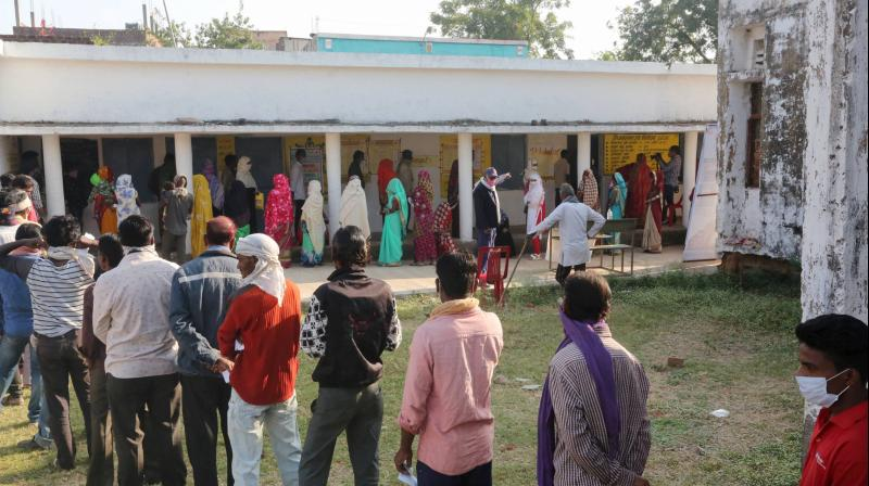 Raisen: People stand in a queue to cast their votes during the Madhya Pradesh Assembly bypolls, amid the ongoing coronavirus pandemic, in Raisen district, Tuesday, Nov. 3, 2020. (PTI Photo)