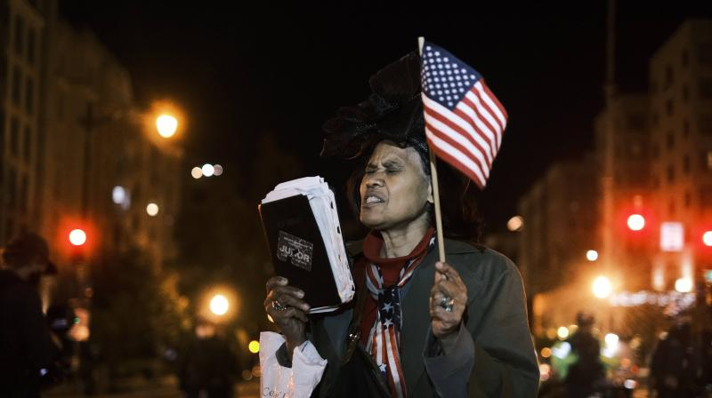 A woman holds up a bible and an American flag on November 3, 2020 in Washington, DC. After a record-breaking early voting turnout, Americans head to the polls on the last day to cast their vote for incumbent U.S. President Donald Trump or Democratic nominee Joe Biden in the 2020 presidential election.