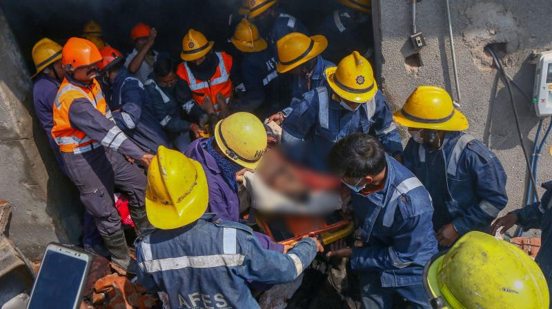 Fire fighters in rescue efforts at the site on Wednesday. (PTI)
