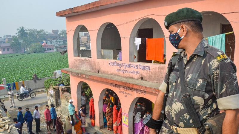 A security official keeps a vigil as voters stand in queues to cast their votes at a polling station during the third phase of Bihar Assembly Elections, in Muzaffarpur district, Saturday, Nov. 7, 2020.  (PTI)
