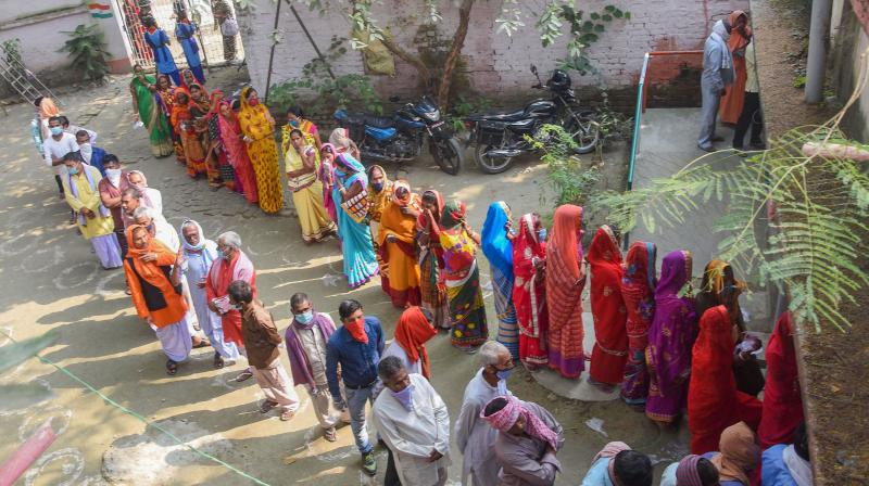 Voters stand in queues to cast their votes at a polling station during the third phase of Bihar Assembly Elections, at Mahua in Vaishali district, Saturday, Nov. 7, 2020. (PTI Photo)