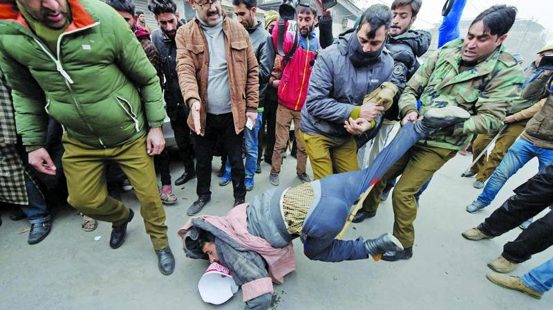 Policemen detain a protester in Srinagar on Thursday during a rally against the government's decision to issue nativity certificates to West Pakistani refugees. (Photo: PTI)
