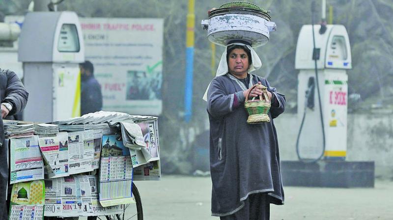 A Kashmiri fisherwoman warms herself on a fire-pot in Srinagar. (Photo: AP/File)