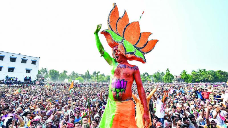 A BJP supporter dons the party symbol as a headgear during Prime Minister Narendra Modi's address at Taherpur in Nadia on Wednesday. (Photo: PTI)