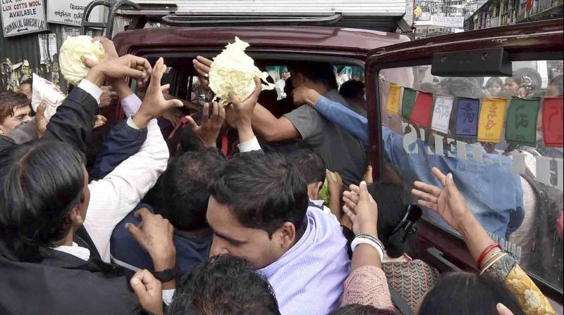 NGO people are dristibuting green vegetables during GJM indefinite strike in Darjeeling on Saturday. (Photo: PTI)