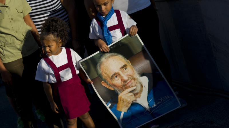 A child holds a portrait of Fidel Castro as mourners arrive to visit the memorial site for the late leader at the Revolution Plaza in Havana, Cuba. (Photo: AP)