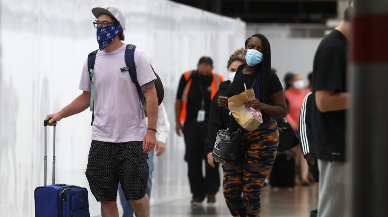 Travellers wear face masks as they arrive in the main terminal of Denver International Airport. AP photo