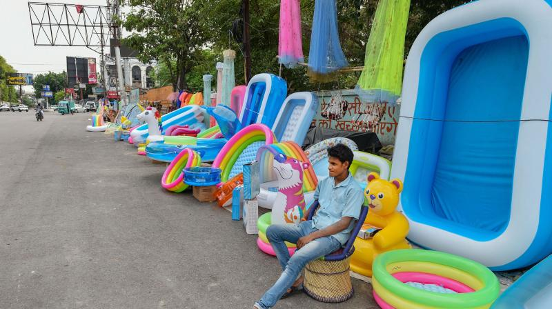 Roadside vendors selling inflatable pools and other items wait for customers, as shops are being opened gradually amid ongoing COVID-19 lockdown. PTI Photo