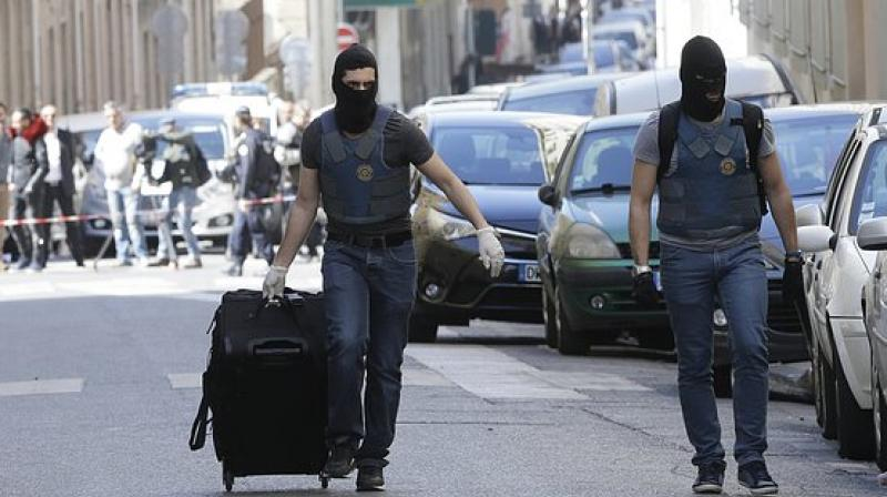 A hooded elite police officer pulls a suitcase after searches in Marseille, southern France, Tuesday, April 18, 2017. (Photo: AP)