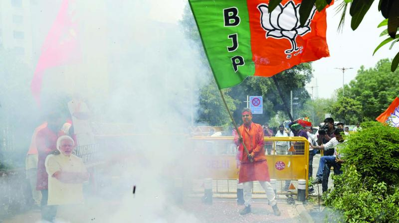 BJP workers light firecrackers outside the party headquarters in New Delhi on Thursday. (Photo: AP)