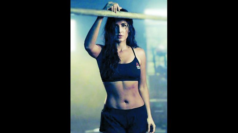 Kat's fitness routine includes box jumps, reverse lunges, jump squats, squat and press, deadlifts, drop push-ups and more.