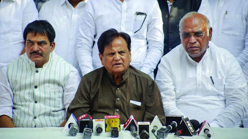 Congress leader Ahmed Patel, flanked by party leaders K.C. Venugopal Rao and Mallikarjun Kharge, addresses a press conference in Mumbai on Saturday. 	(Photo: PTI)
