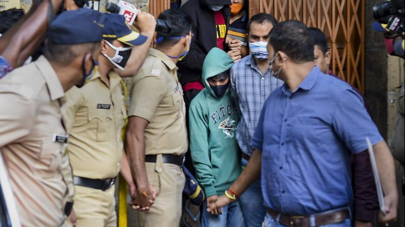 Sushant's chef Dipesh Sawant (green) being taken to court by NCB officers for a hearing in connection with death by suicide case of the bollywood actor, in Mumbai. — PTI photo