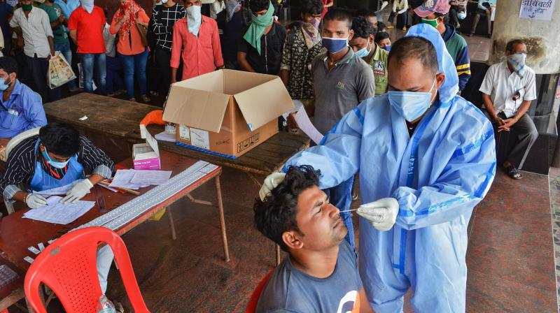 A medic collects a nasal sample from a migrant worker via Rapid Antigen kit for COVID-19 test, before he boards a bus to reach his workplace, at Thane Central Bus Stand, in Thane.— PTI photo