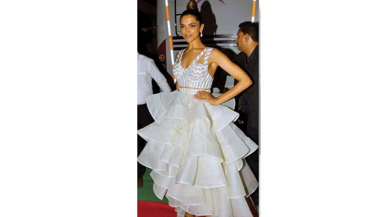 Deepika Padukone pairs a blingy crop top with a white ruffled skirt.